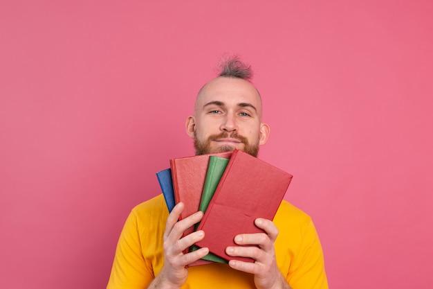 Volwassen lachende vrijetijdskleding man met baard hugs favoriete boeken voor zichzelf geïsoleerd op roze