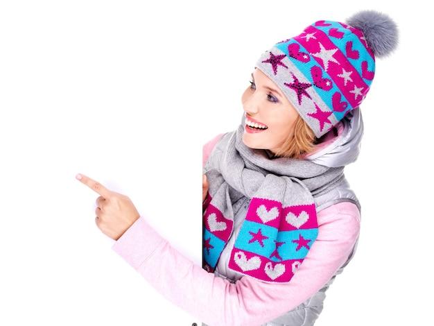 Volwassen lachende vrouw in winter bovenkleding houdt het witte bordje in handen en wijst erop