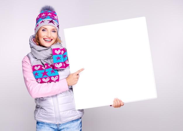 Volwassen lachende vrouw in winter hoed houdt het witte bordje in handen