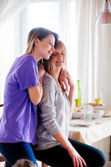 Volwassen lesbisch koppel omarmen thuis in de buurt van talbe met voedsel.