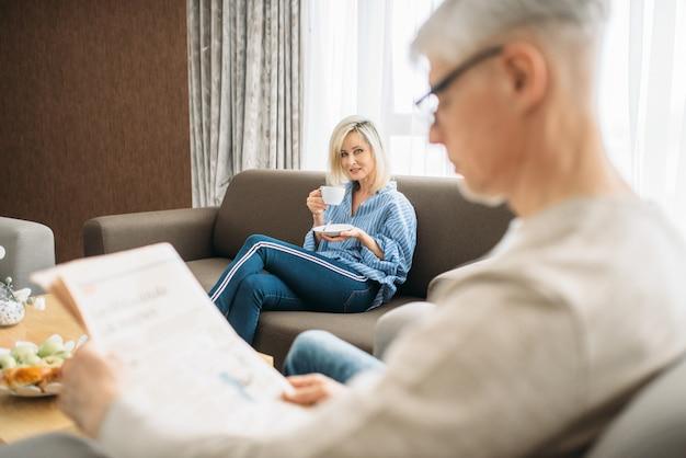 Volwassen liefdepaar thuis in de ochtend, man leest krant, vrouw drinkt koffie. rijpe man en vrouw zittend op de bank, gelukkige familie