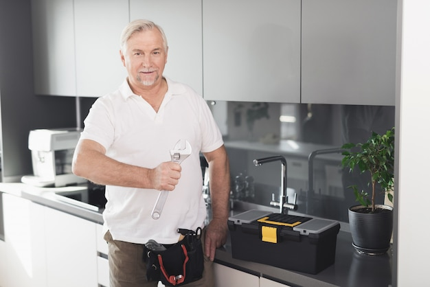 Volwassen loodgieter met een moersleutel keuken poseren.