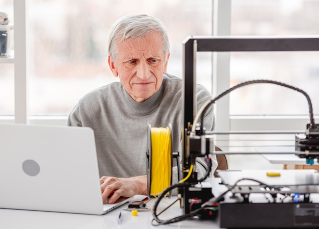 Volwassen man aan het werk op laptop met ontwerpproject en kijken naar moderne 3d-printer
