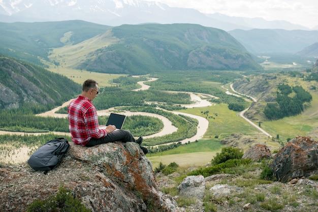 Volwassen man aan het werk op zijn computer op de top van een berg met prachtig uitzicht