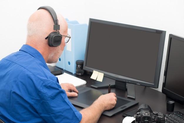 Volwassen man aan het werk op zijn grafisch tablet