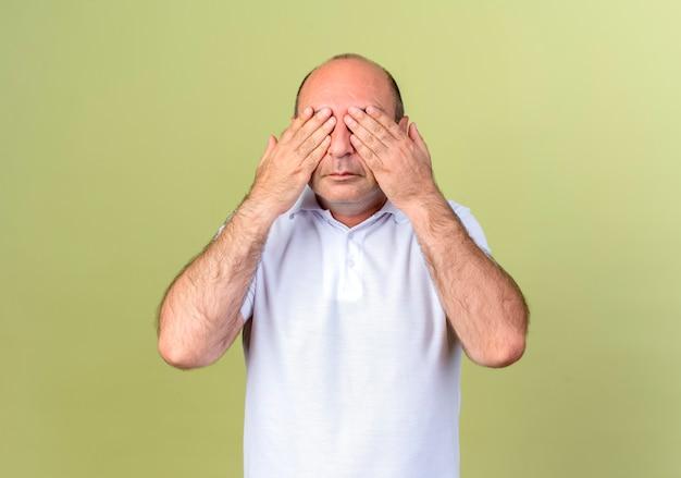Volwassen man bedekt ogen met hand geïsoleerd op olijfgroene muur