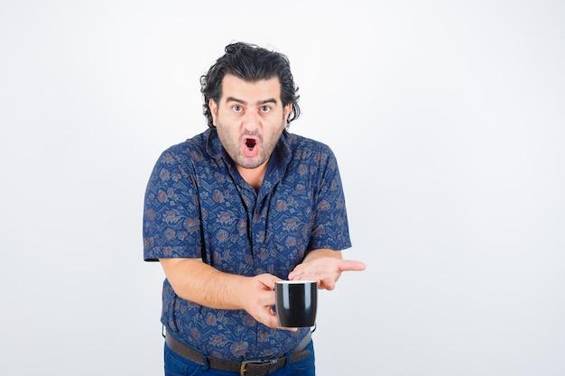 Volwassen man beker in shirt tonen en boos kijken. vooraanzicht.