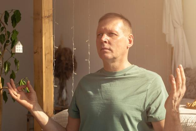 Volwassen man beoefenen van yoga en mediteren in gezellige eco-stijl huis in meditatiehouding