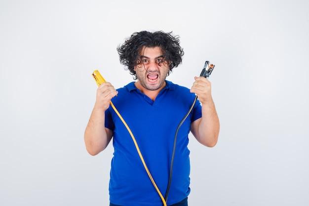 Volwassen man bouwgereedschap in blauw t-shirt te houden en gek op zoek. vooraanzicht.