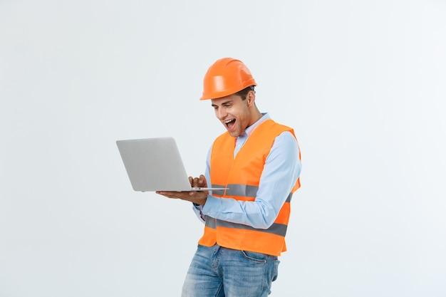 Volwassen man constructeur verrast en werken met laptop in helm binnenshuis.