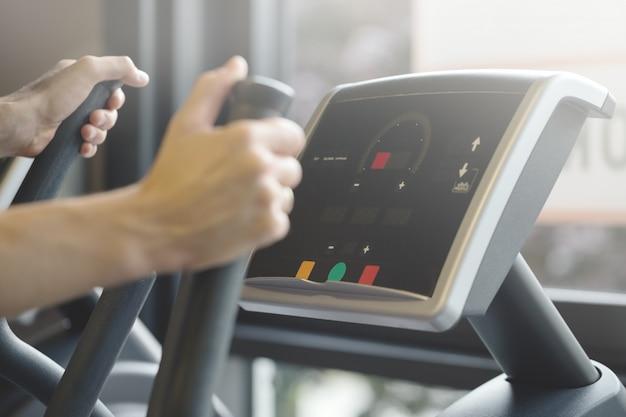 Volwassen man die cardio-oefeningen in de fitnessclub maakt