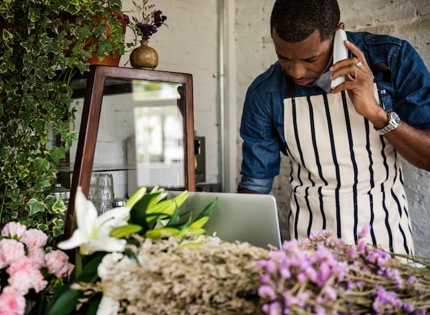 Volwassen man die een bestelling ontvangt, belt in flora shop