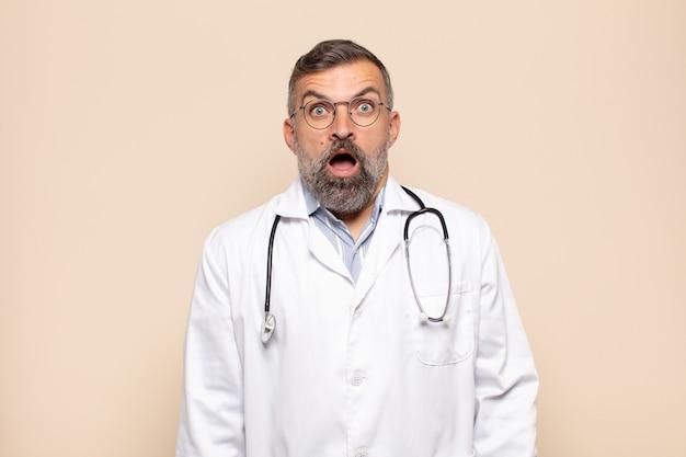 Volwassen man die erg geschokt of verrast kijkt, starend met open mond en zegt wow