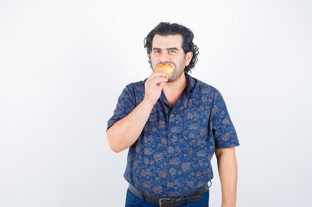 Volwassen man die gebakjesproduct eet terwijl hij naar de camera in hemd kijkt en verheugd, vooraanzicht kijkt.