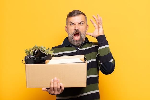 Volwassen man die met de handen in de lucht schreeuwt, zich woedend, gefrustreerd, gestrest en boos voelt
