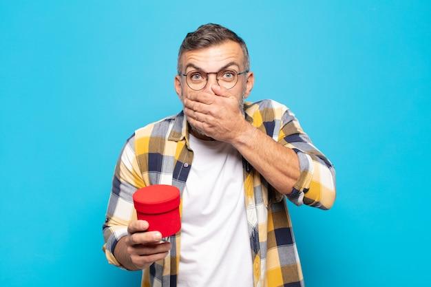 Volwassen man die mond bedekt met handen met een geschokte, verbaasde uitdrukking, een geheim bewaren of oeps zeggen