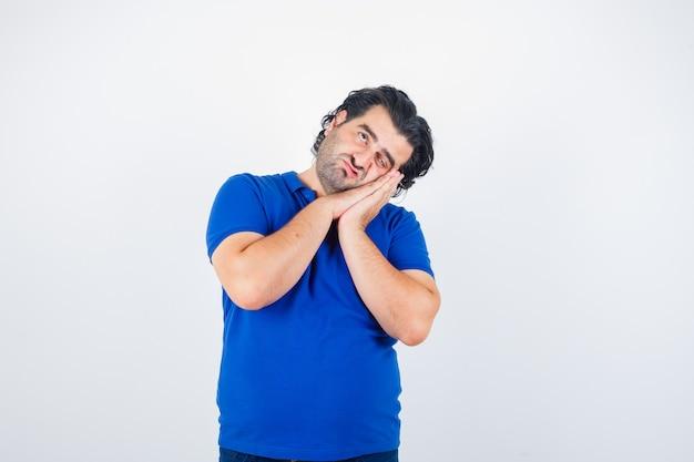 Volwassen man die op handpalmen als hoofdkussen in blauw t-shirt leunt en nadenkend kijkt. vooraanzicht.