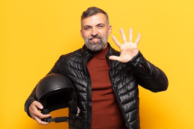 Volwassen man die vriendelijk glimlacht en kijkt, nummer vijf of vijfde met vooruit hand toont, aftellend