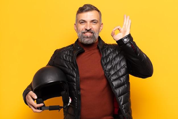 Volwassen man die zich gelukkig, ontspannen en tevreden voelt, goedkeuring toont met een goed gebaar, glimlachend