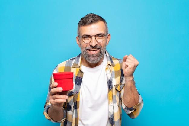 Volwassen man die zich geschokt, opgewonden en gelukkig voelt, lacht en succes viert, zeggend wow!