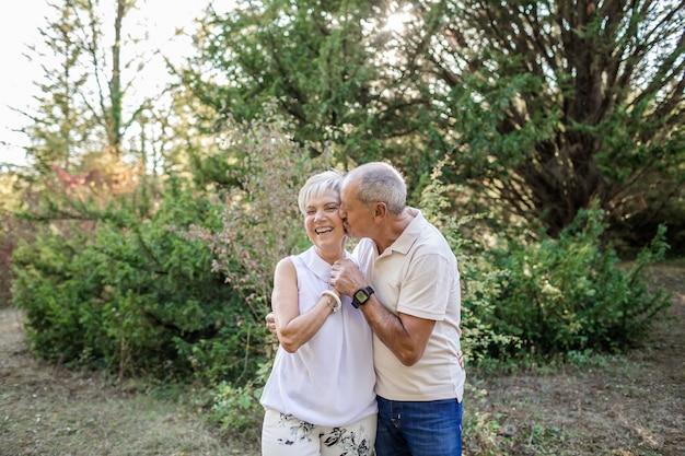 Volwassen man die zijn vrouw kust terwijl ze hem knuffelt en ze lacht tijdens een wandeling in het bos bij zonsondergang.