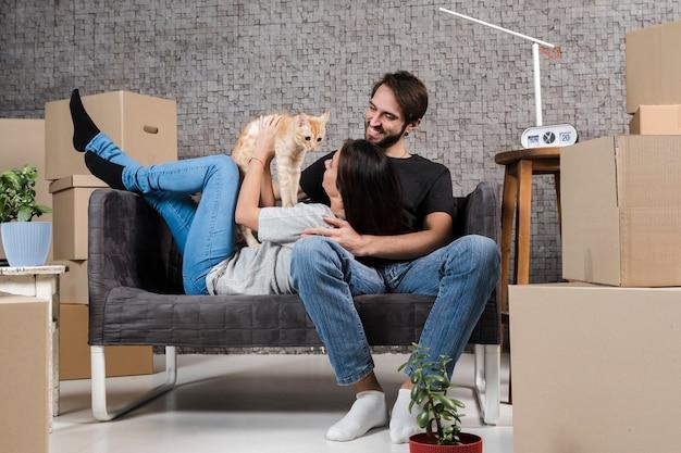 Volwassen man en vrouw binnenshuis met familie kat
