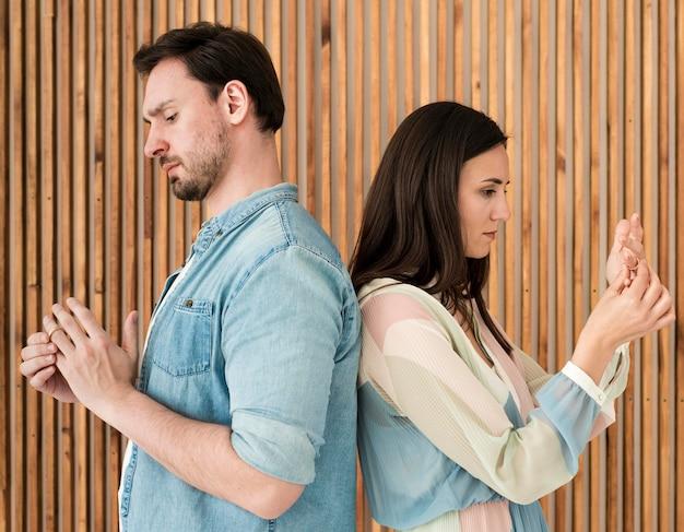 Volwassen man en vrouw die trouwringen opstijgen