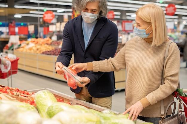 Volwassen man en vrouw in vrijetijdskleding en beschermende maskers die verse rijpe tomaten in de supermarkt kiezen terwijl ze bij een groot display staan