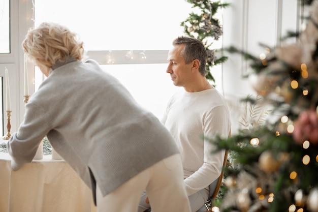 Volwassen man en vrouw knuffelen in de buurt van de feesttafel in de hal met een kerstboom