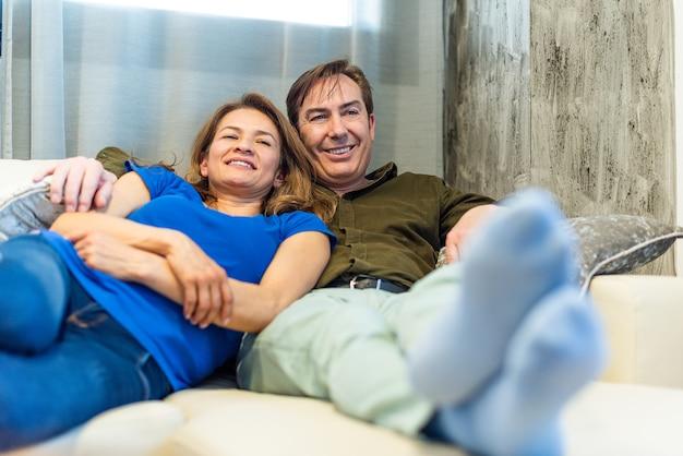 Volwassen man en vrouw liggen op de bank tv te kijken. hoge kwaliteit foto