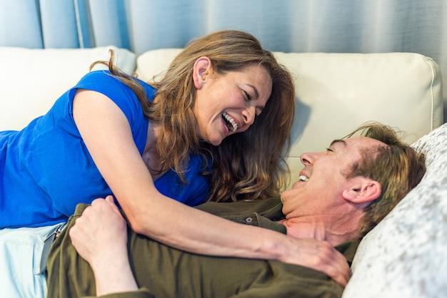 Volwassen man en vrouw liggend op de bank knuffelen. hoge kwaliteit foto