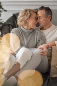 Volwassen man en vrouw zitten op de grond bij de bank en knuffelen