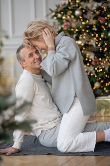 Volwassen man en vrouw zitten op de grond bij de kerstboom en knuffelen