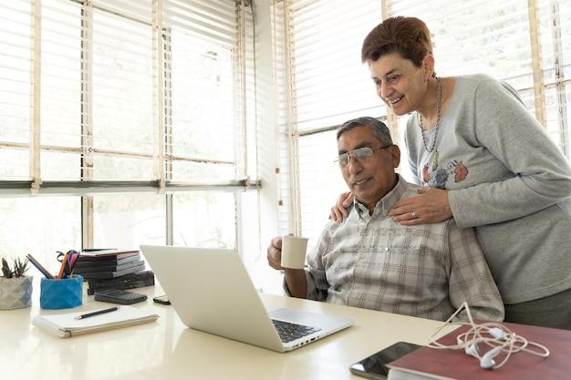 Volwassen man en zijn vrouw kijken naar laptop.