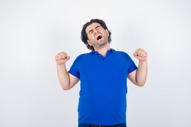Volwassen man geeuwen en rekken in blauw t-shirt en slaperig op zoek. vooraanzicht.