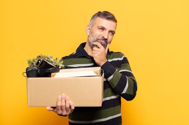 Volwassen man glimlachend met een gelukkige, zelfverzekerde uitdrukking met de hand op de kin, zich afvragend en opzij kijkend