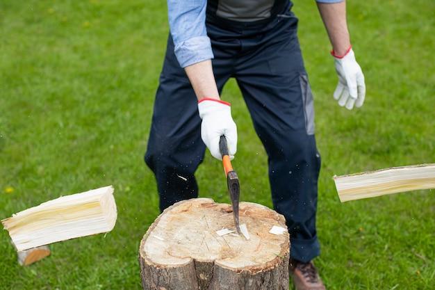 Volwassen man hakt hout met bijl