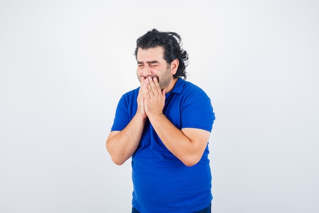 Volwassen man hand in hand op mond in blauw t-shirt en treurig op zoek. vooraanzicht.