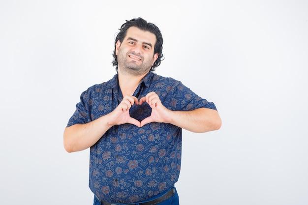 Volwassen man hart gebaar in shirt tonen en op zoek gelukkig. vooraanzicht.