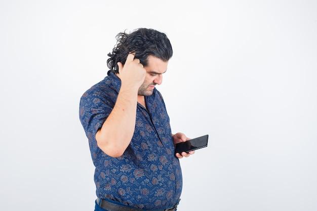 Volwassen man hoofd krabben terwijl mobiele telefoon in shirt en op zoek attent. vooraanzicht.