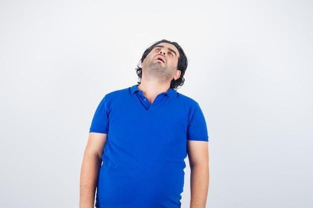 Volwassen man hoofd terug in blauw t-shirt buigen en slaperig op zoek. vooraanzicht.