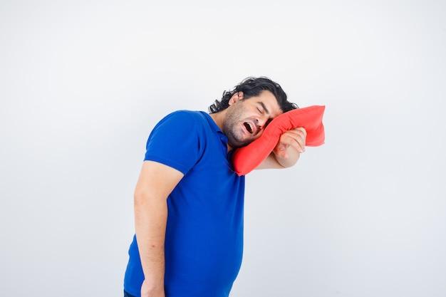 Volwassen man in blauw t-shirt leunend hoofd op kussen terwijl geeuwen en op zoek slaperig, vooraanzicht.