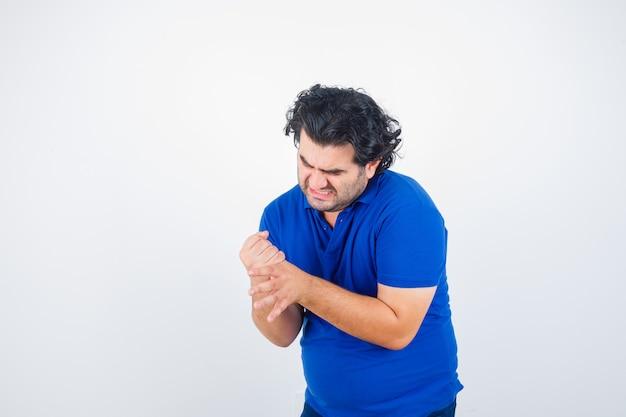 Volwassen man in blauw t-shirt met zijn pijnlijke hand en op zoek verontrust, vooraanzicht.