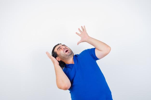 Volwassen man in blauw t-shirt, spijkerbroek opheffen dient bang manieren in en kijkt bang, vooraanzicht.