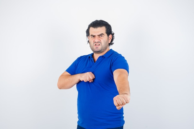 Volwassen man in blauw t-shirt, spijkerbroek staande in strijd pose en op zoek boos, vooraanzicht.