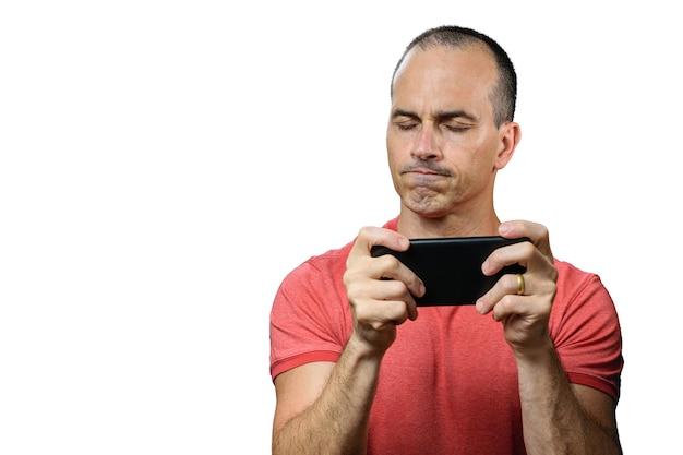 Volwassen man in casual outfit, teleurgesteld, ogen gesloten en smartphone vast te houden.