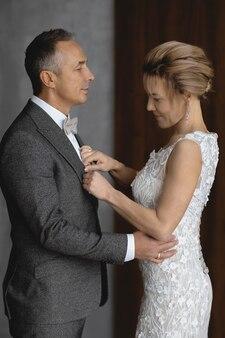 Volwassen man in een grijs pak en zijn bruid op trouwdag