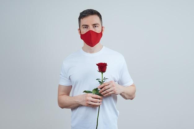 Volwassen man in een rood beschermend masker, met een roos in zijn hand, op een grijze achtergrond, studio-opname. valentijnsdag in quarantaine.