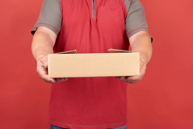 Volwassen man in een rood t-shirt heeft een kartonnen bruine doos op een rode achtergrond