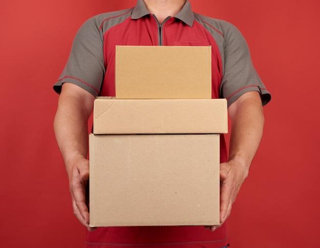 Volwassen man in een t-shirt heeft een stapel grote kartonnen bruine dozen op een rode achtergrond